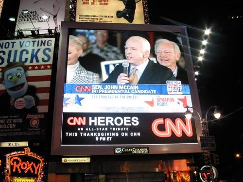 [Not Voting Sucks billboard, McCain and Lieberman on the TV]