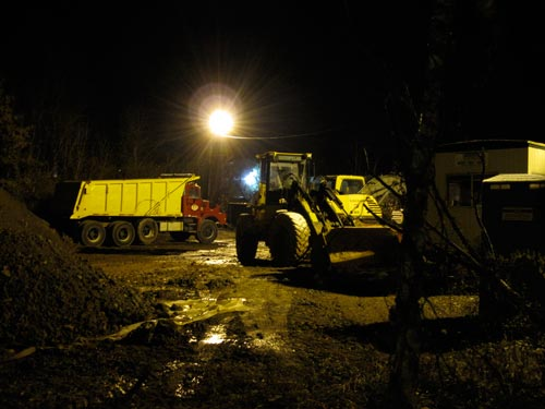 [Caterpillar trucks in the muddy yard at night]