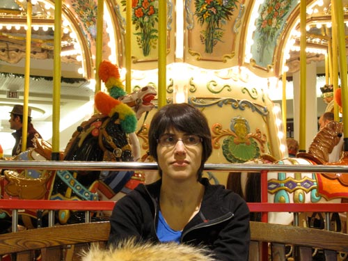 [Elena in front of the carousel]