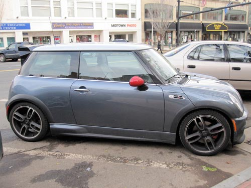 [nose in, angle-parked dark grey Mini Cooper S]