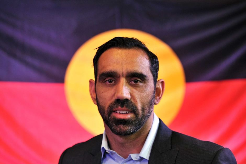 Adam Goodes with Aboriginal flag as backdrop